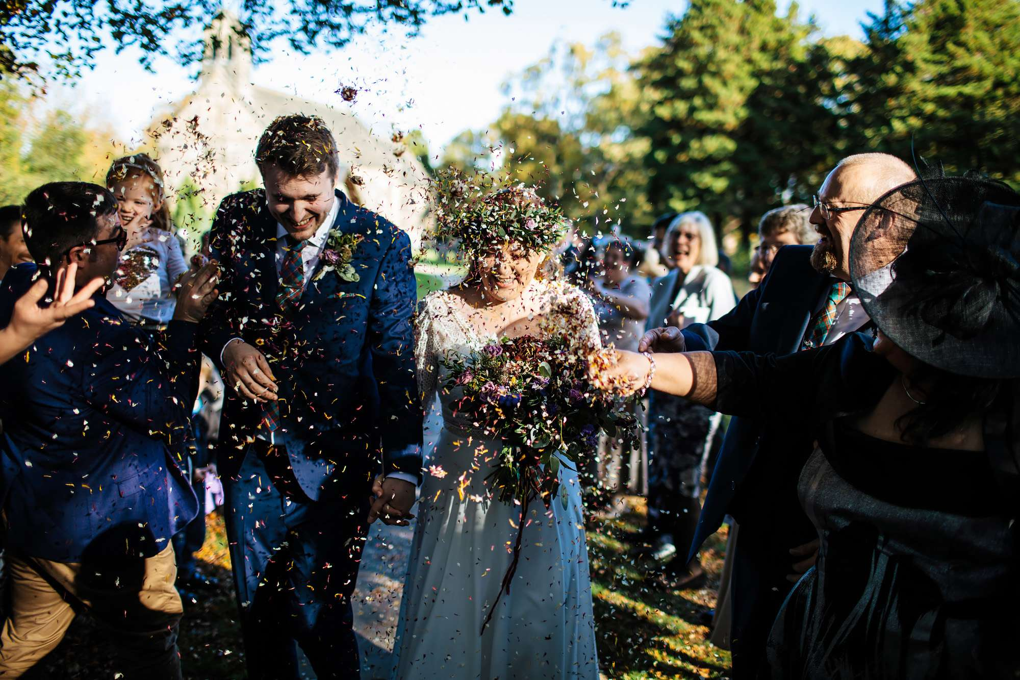 Wedding guests throwing confetti over the bride and groom
