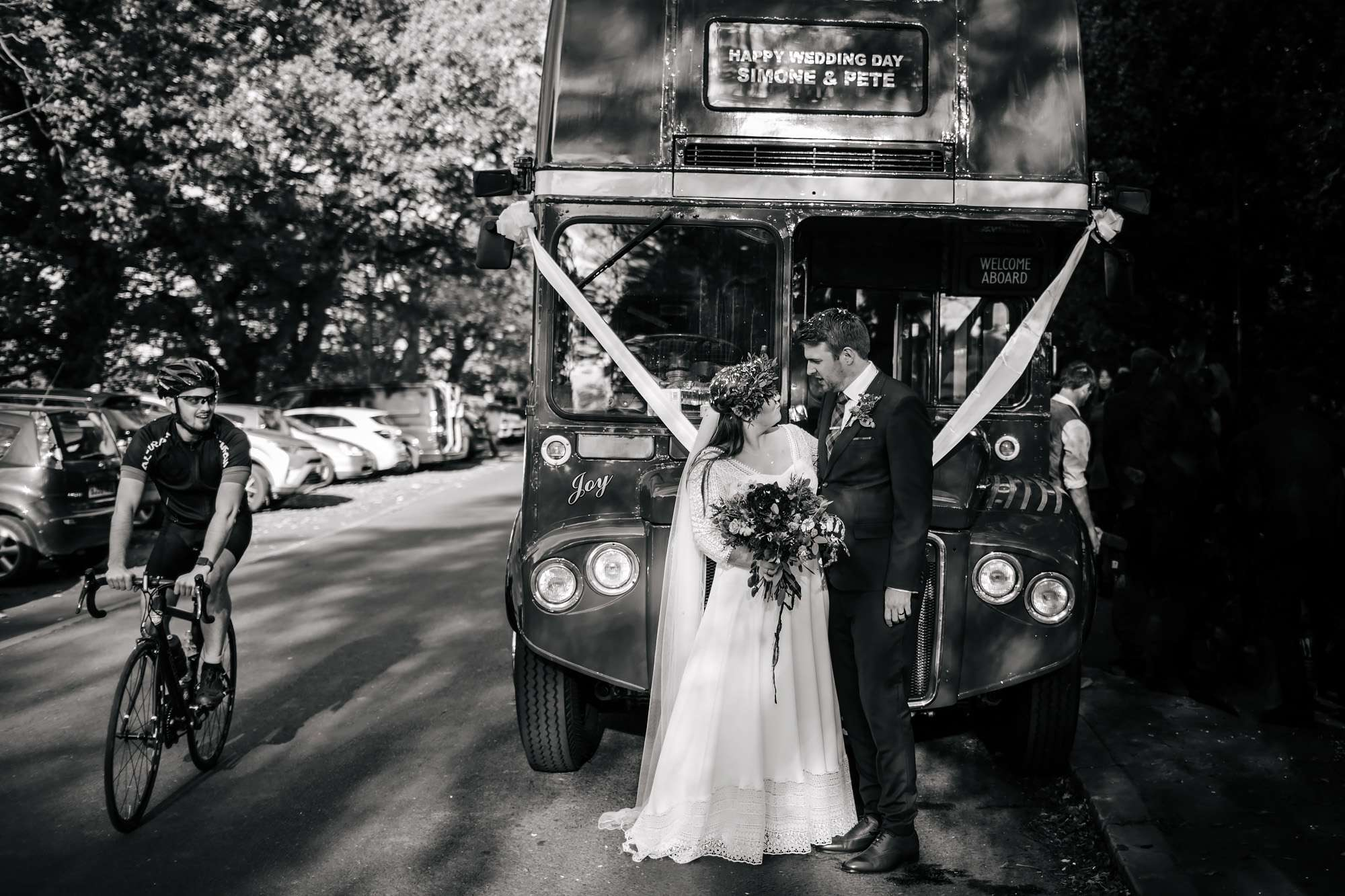 Bride and groom pose in front of their Leeds wedding bus