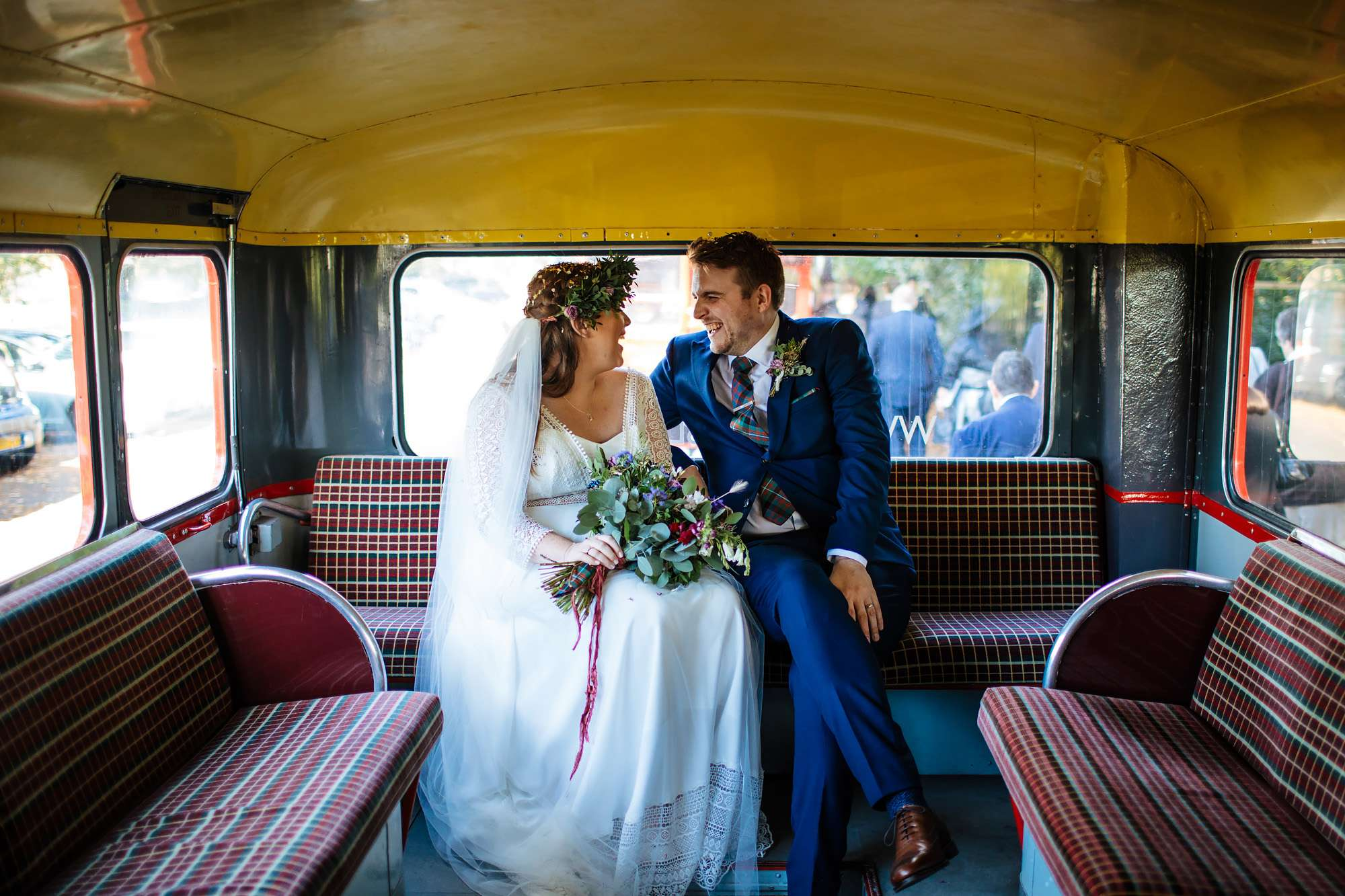 Bride and groom sitting on their vintage bus at a wedding
