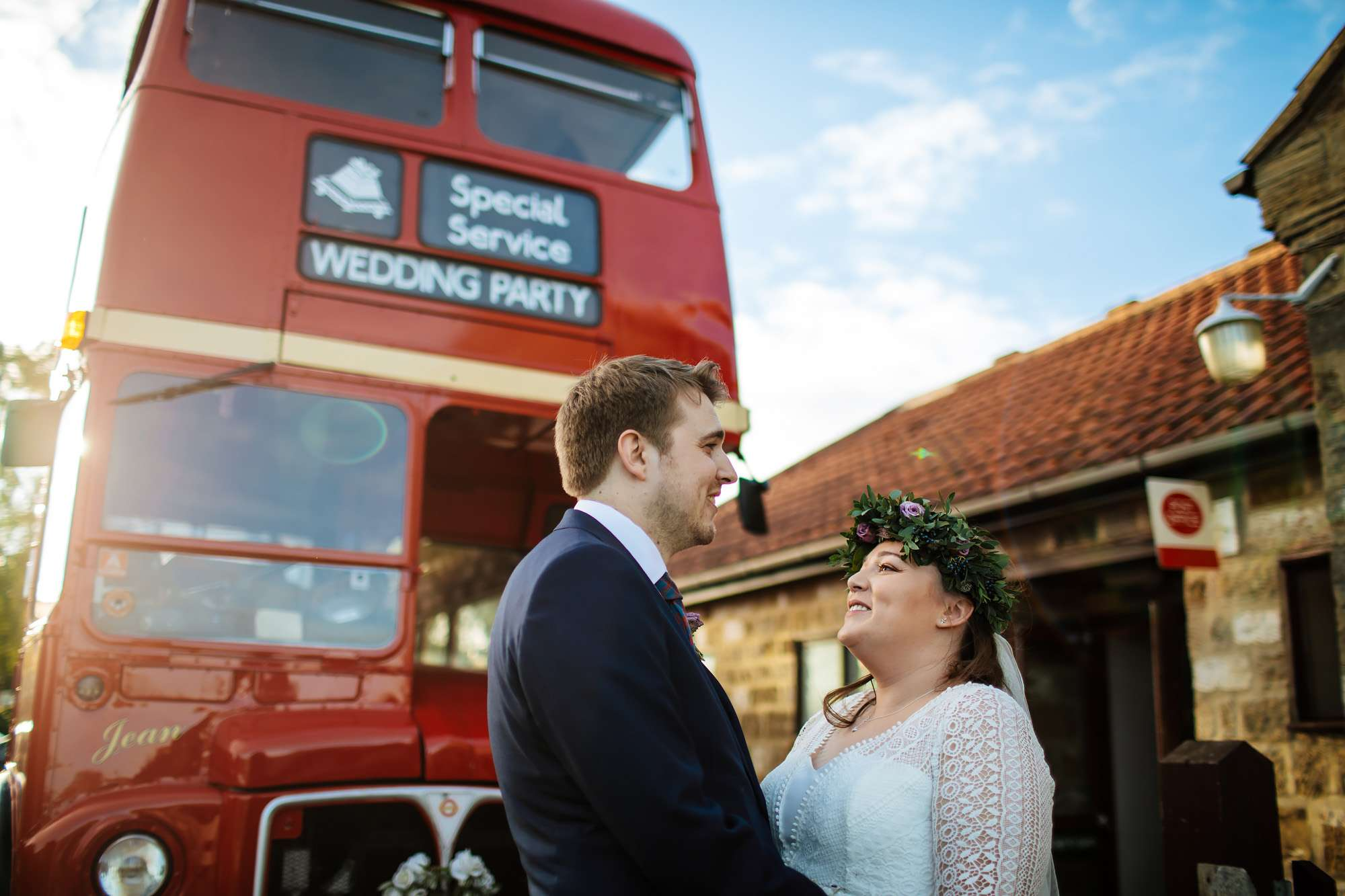 Bride and groom portrait with their bus in the background