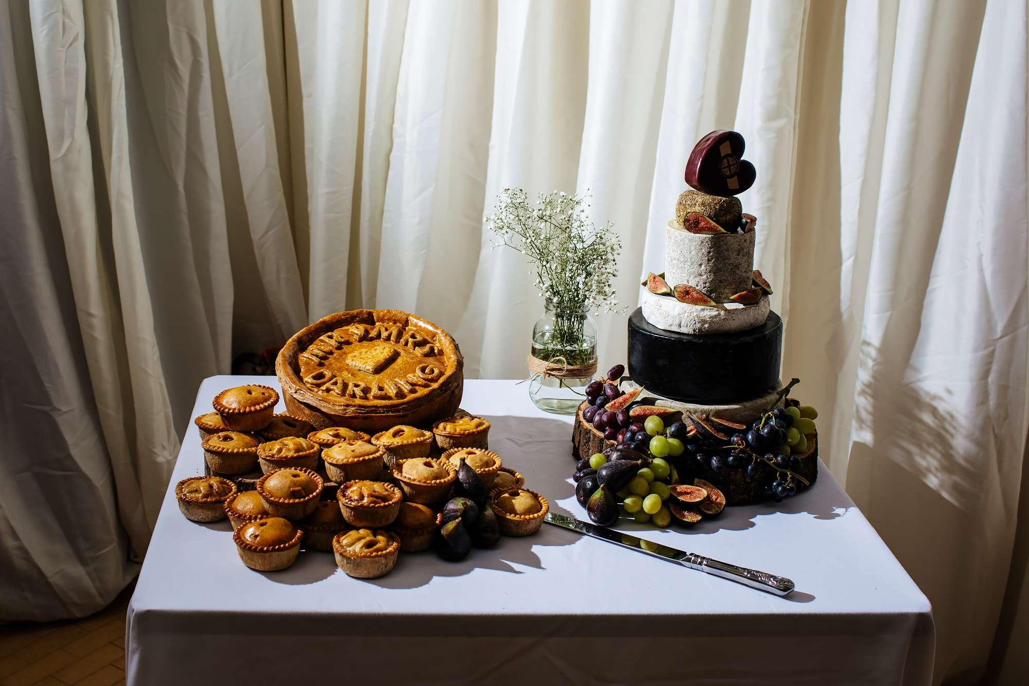 Close up of the wedding cake and pork pie cake at a wedding
