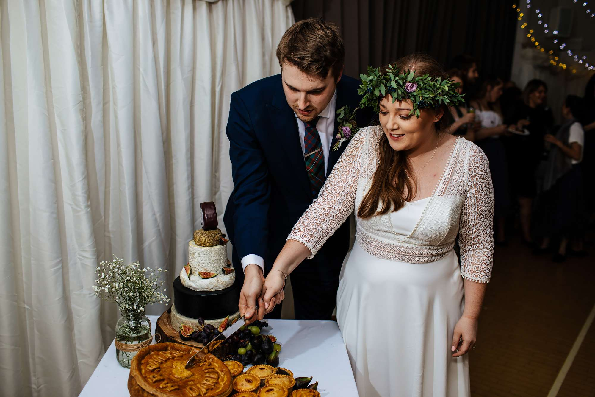 Bride and groom cutting a pork pie cake at East Keswick Village Hall
