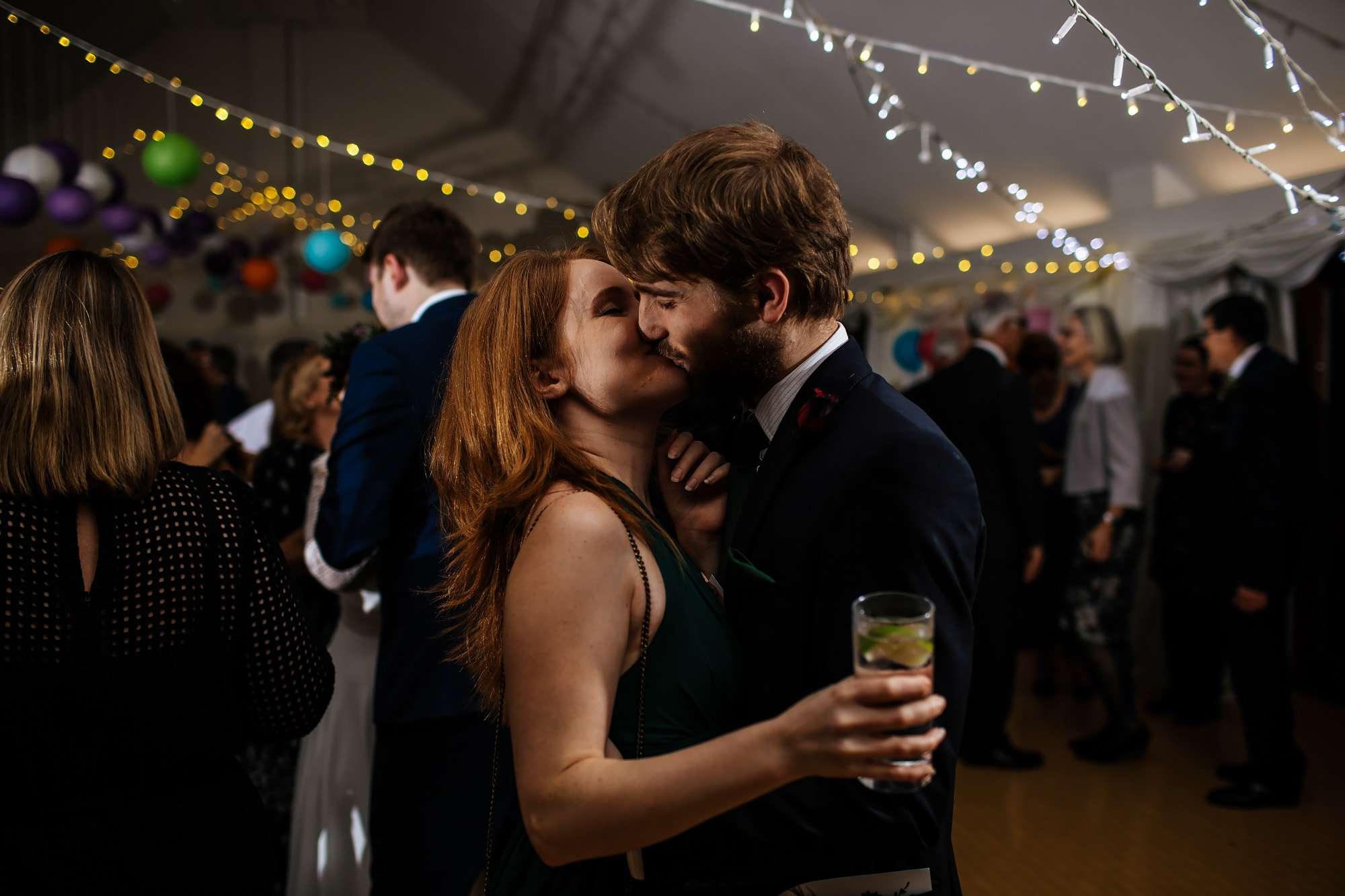 Wedding guests kissing at East Keswick Village Hall Leeds