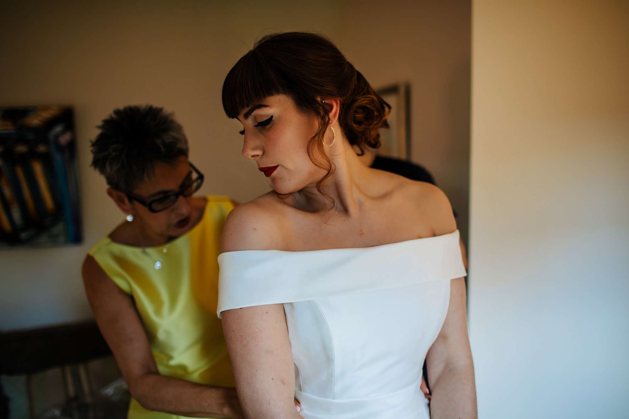 Bride has her dress fastened by her mum on her wedding day