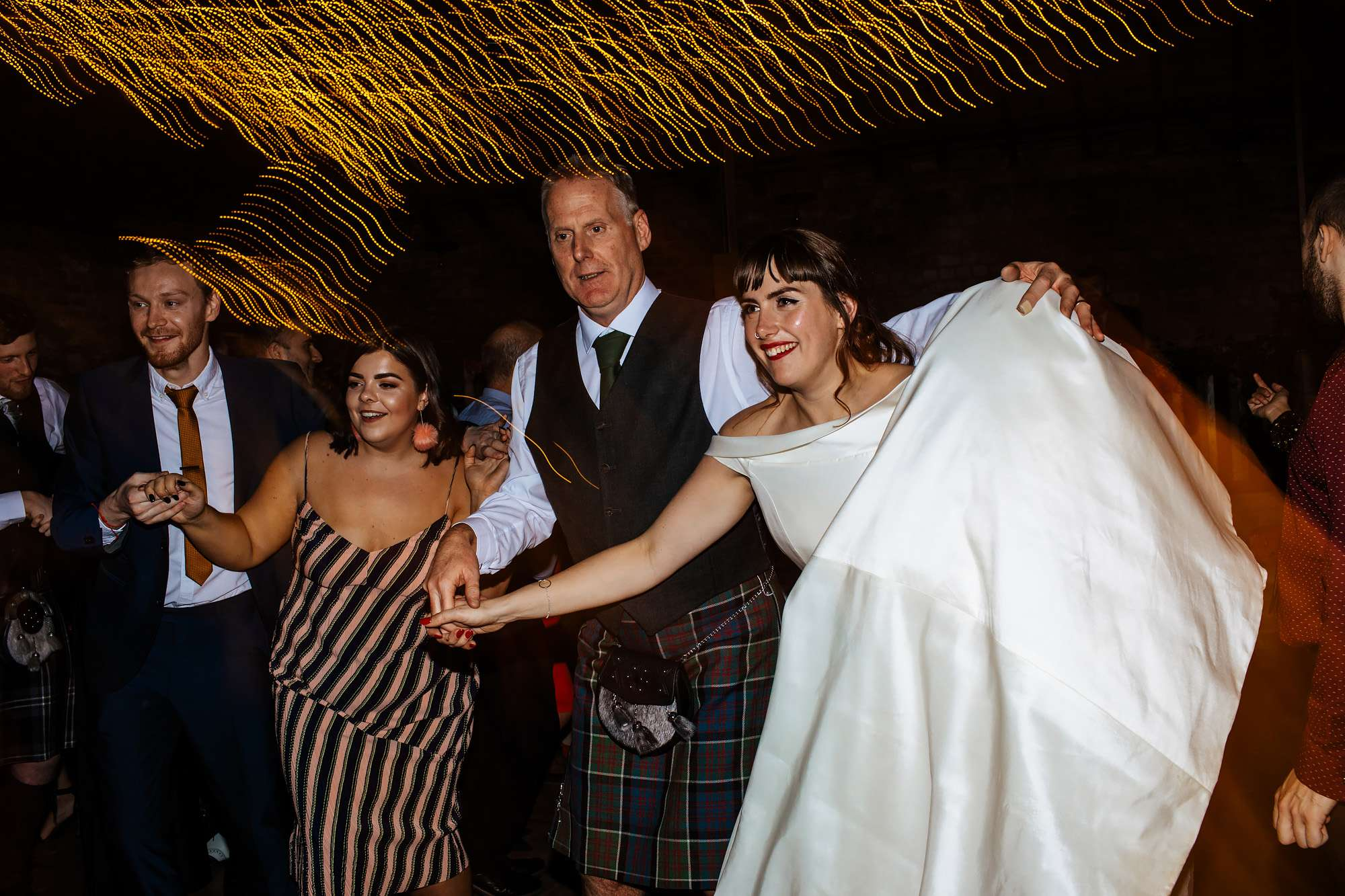 Bride and dad ceilidh dancing at her wedding