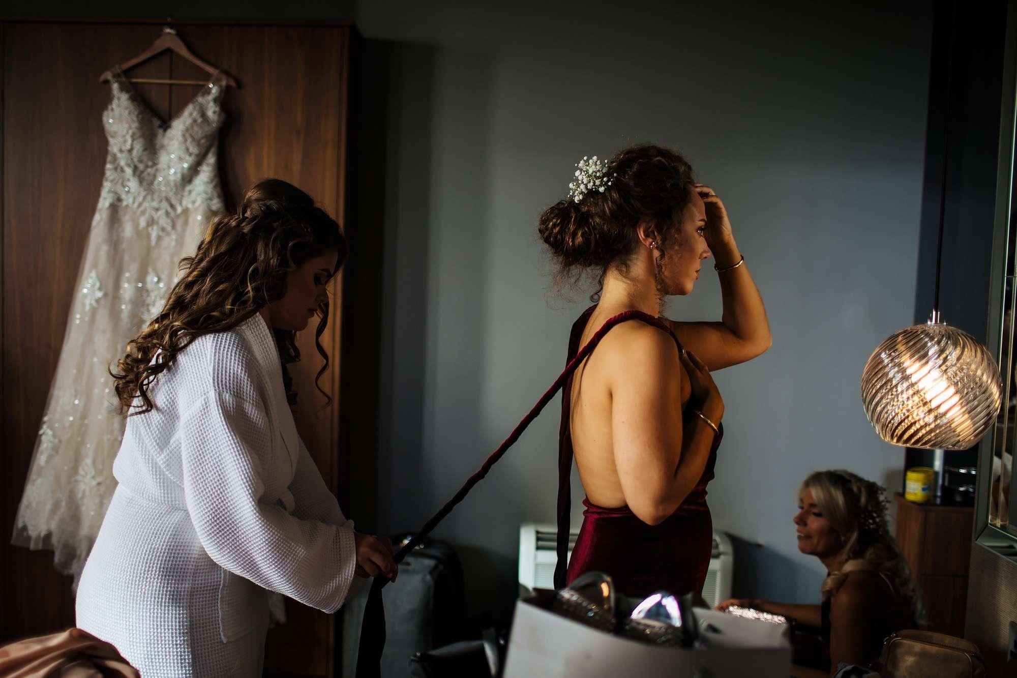 Bride helping a bridesmaid into her dress