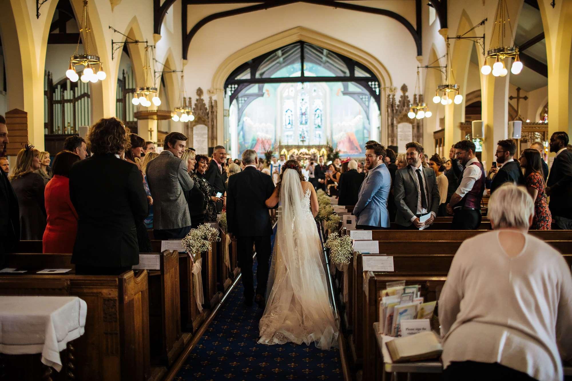 Bride and dad walk down the church aisle