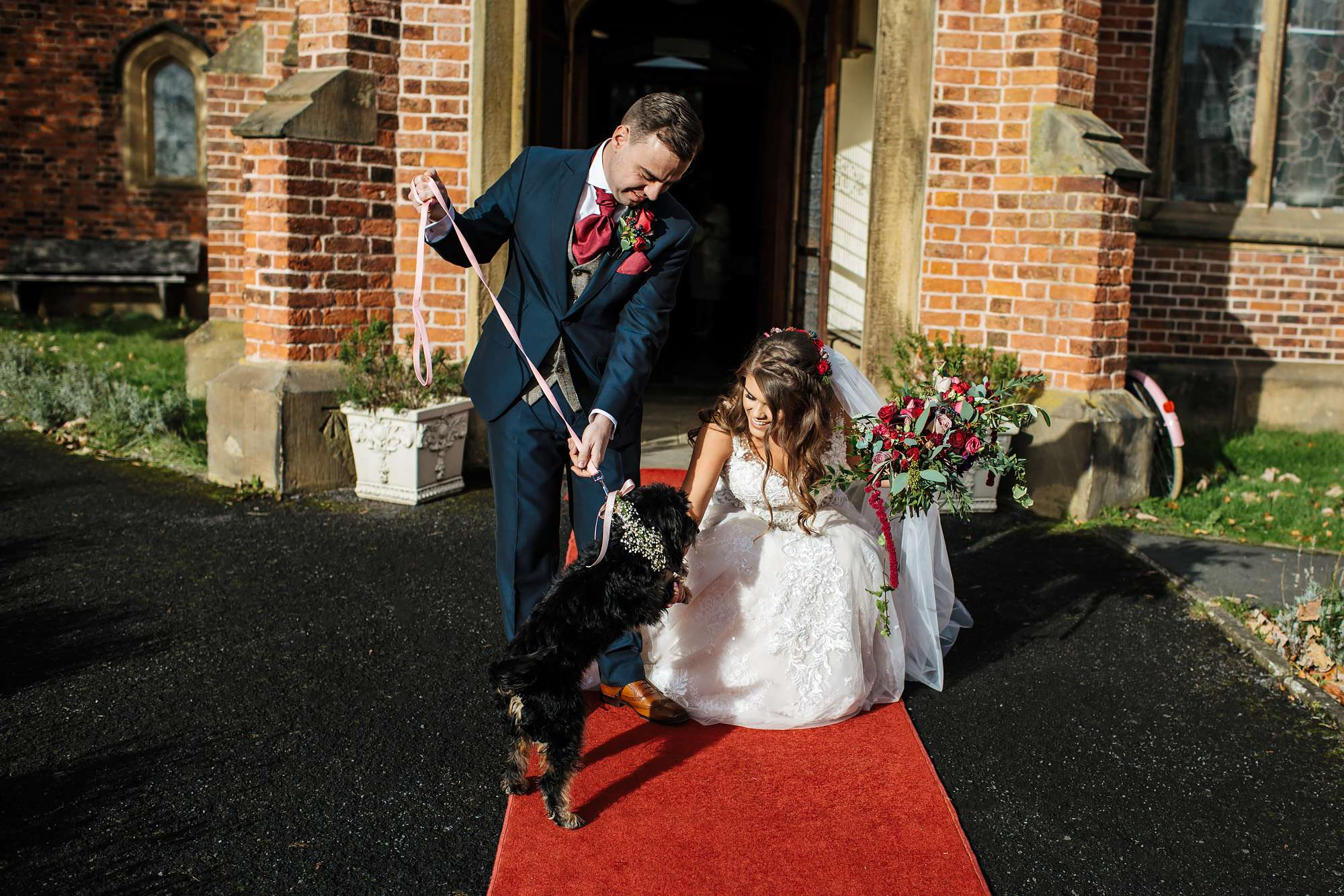Bride and groom pose with their dog at the wedding