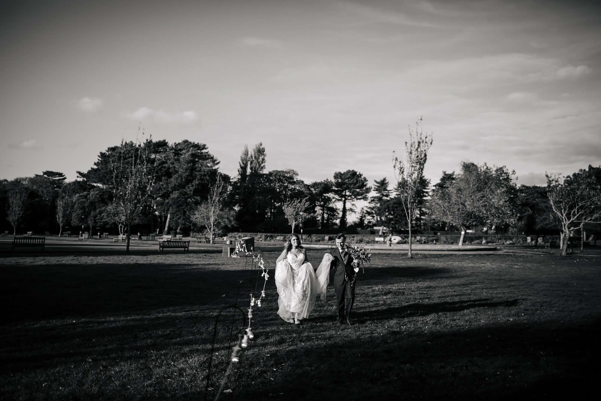 Bride and groom walking through the park at their wedding