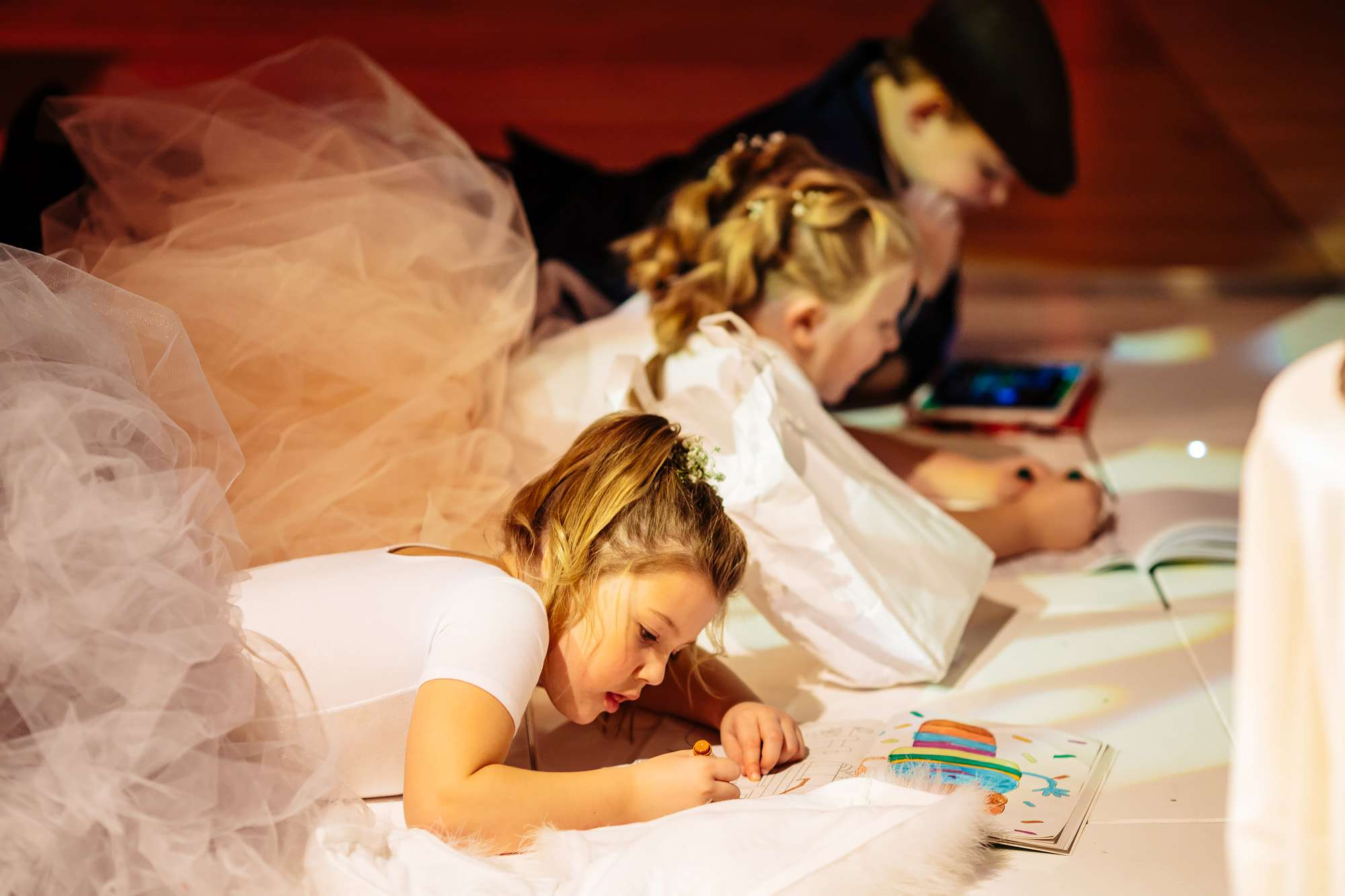 Young kids drawing on the floor at a wedding