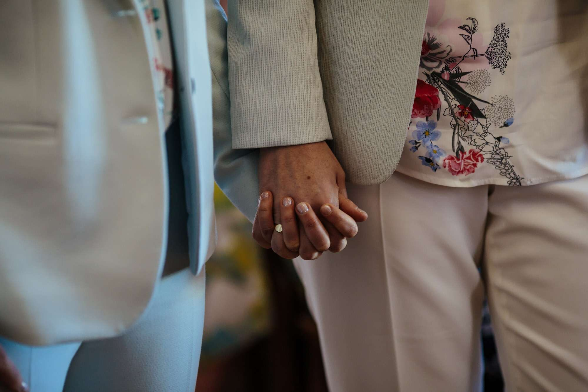 Two brides holding hands during a gay wedding ceremony