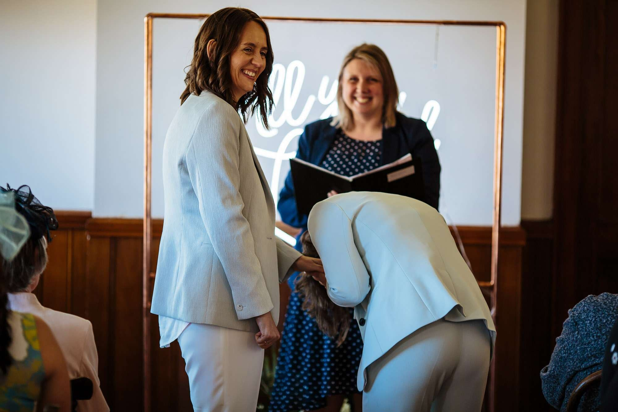 Brides laughing during their gay wedding ceremony