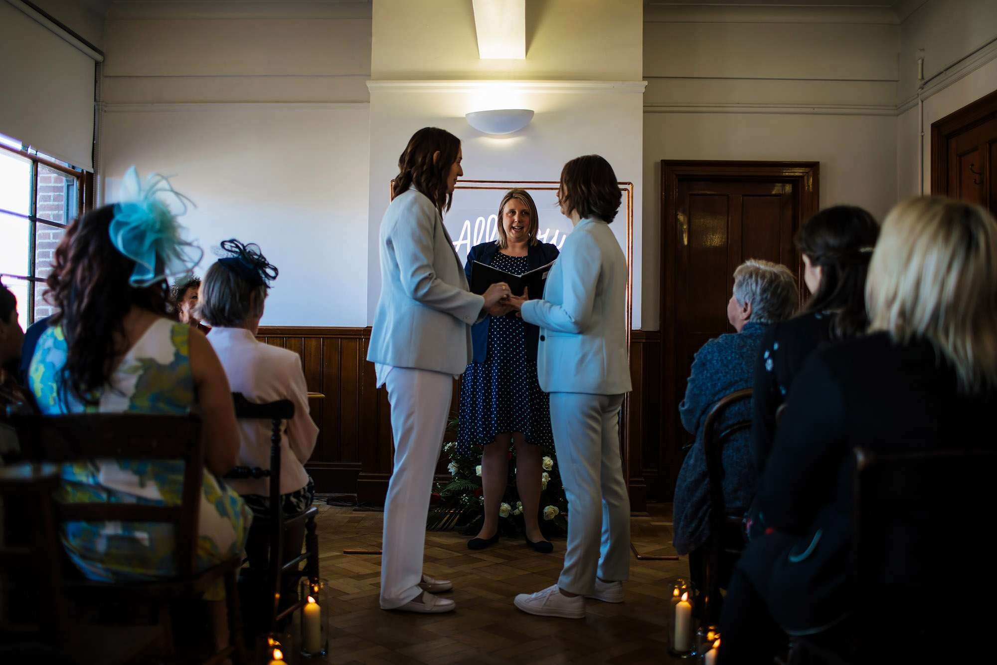 Two brides holding hands at their wedding