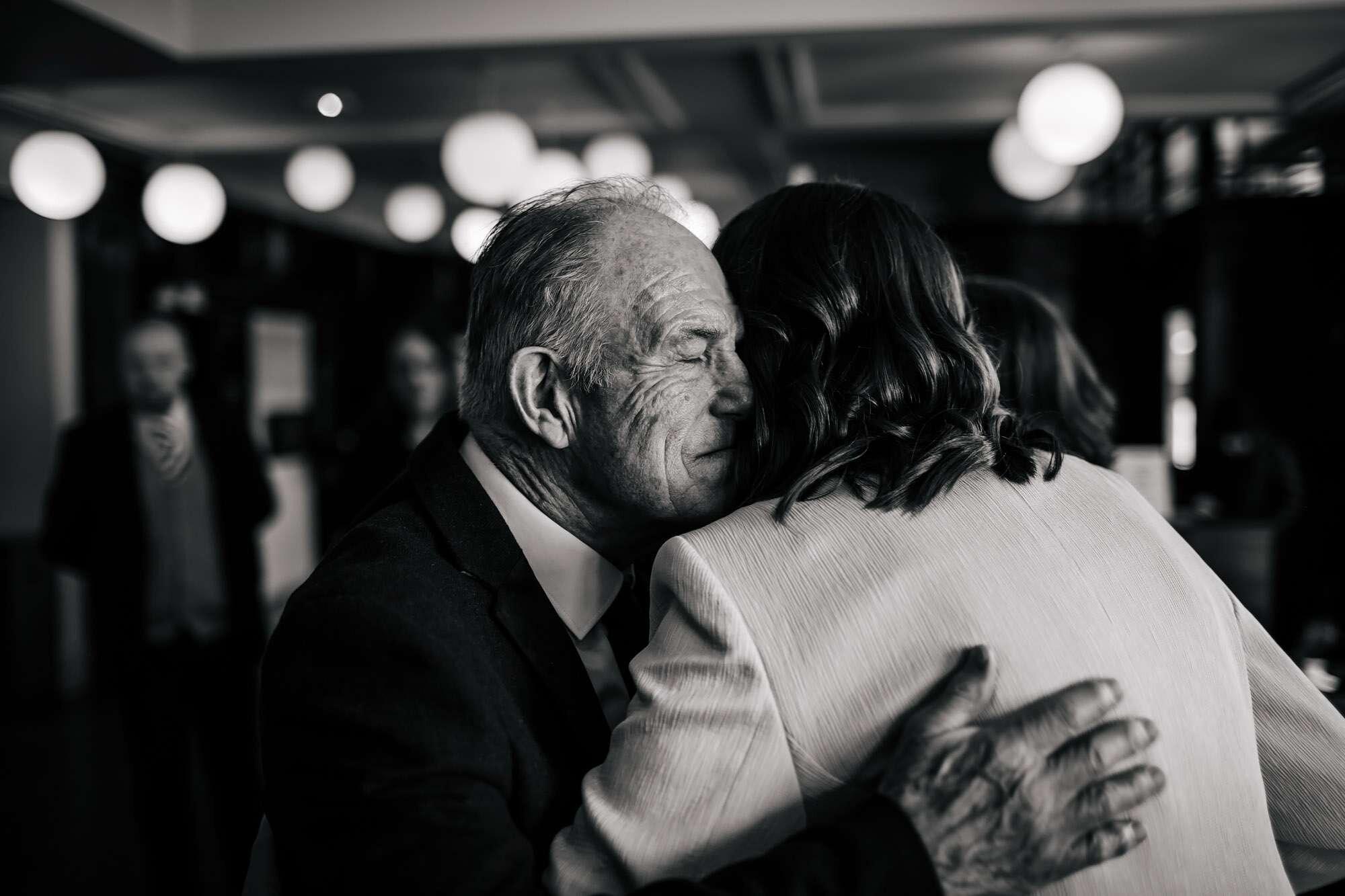 Bride and dad hugging at her gay wedding