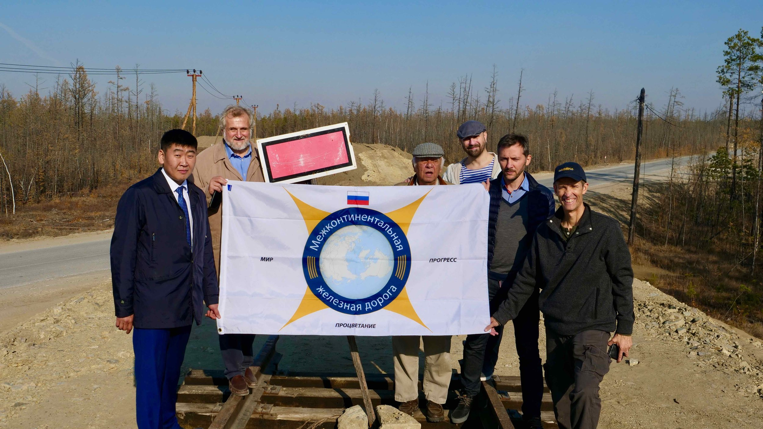The Intercontinental Railway team unveil the Russian version of the ICR flag at the railhead in Nizhny Bestyakh, Siberia. From here, Yakutia Railways is extending the line toward the Bering Strait. From left to right: Alexei Mestnikov (Yakutia Railway), Victor Razbegin (ICR), George Koumal (ICR), Vlad Ketkovich (film producer), Dmitriy Kondratov (Yakutia Railway), Scott Spencer (ICR). During the ceremony, Mr. Koumal and Mr. Spencer presented Mr. Razbegin with an honorary golden spike for his three decades of work researching and promoting the InterContinental Railway in Russia and abroad.