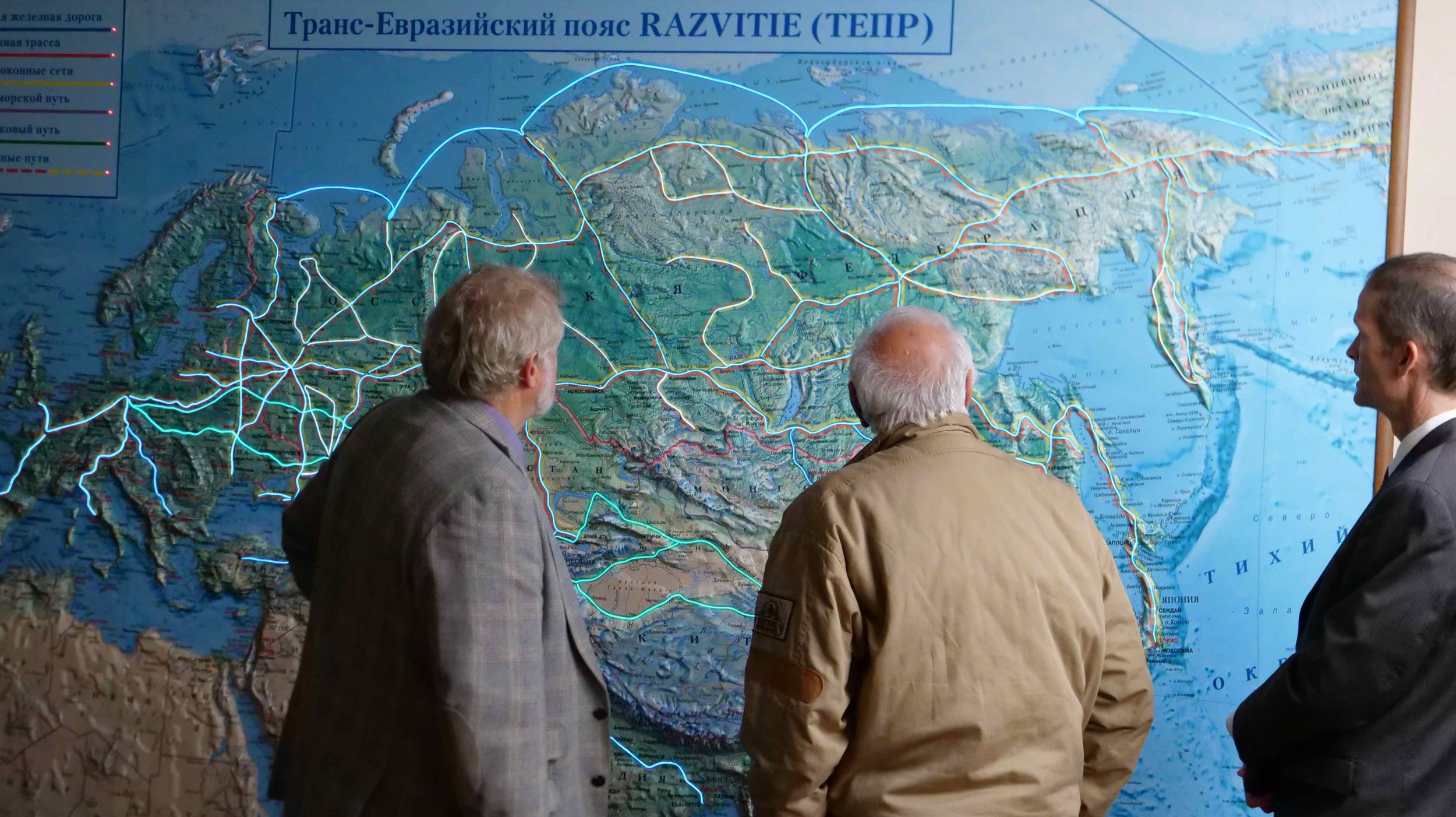 The InterContinental Railway team Victor Razbegin, George Koumal and Scott Spencer examine the map on the wall of the Russian Academy of Sciences showing the current and planned transportation routes in the Russian Federation, Europe and Asia. At the top right is the planned rail connection for the InterContinental Railway across the Bering Strait to Alaska.