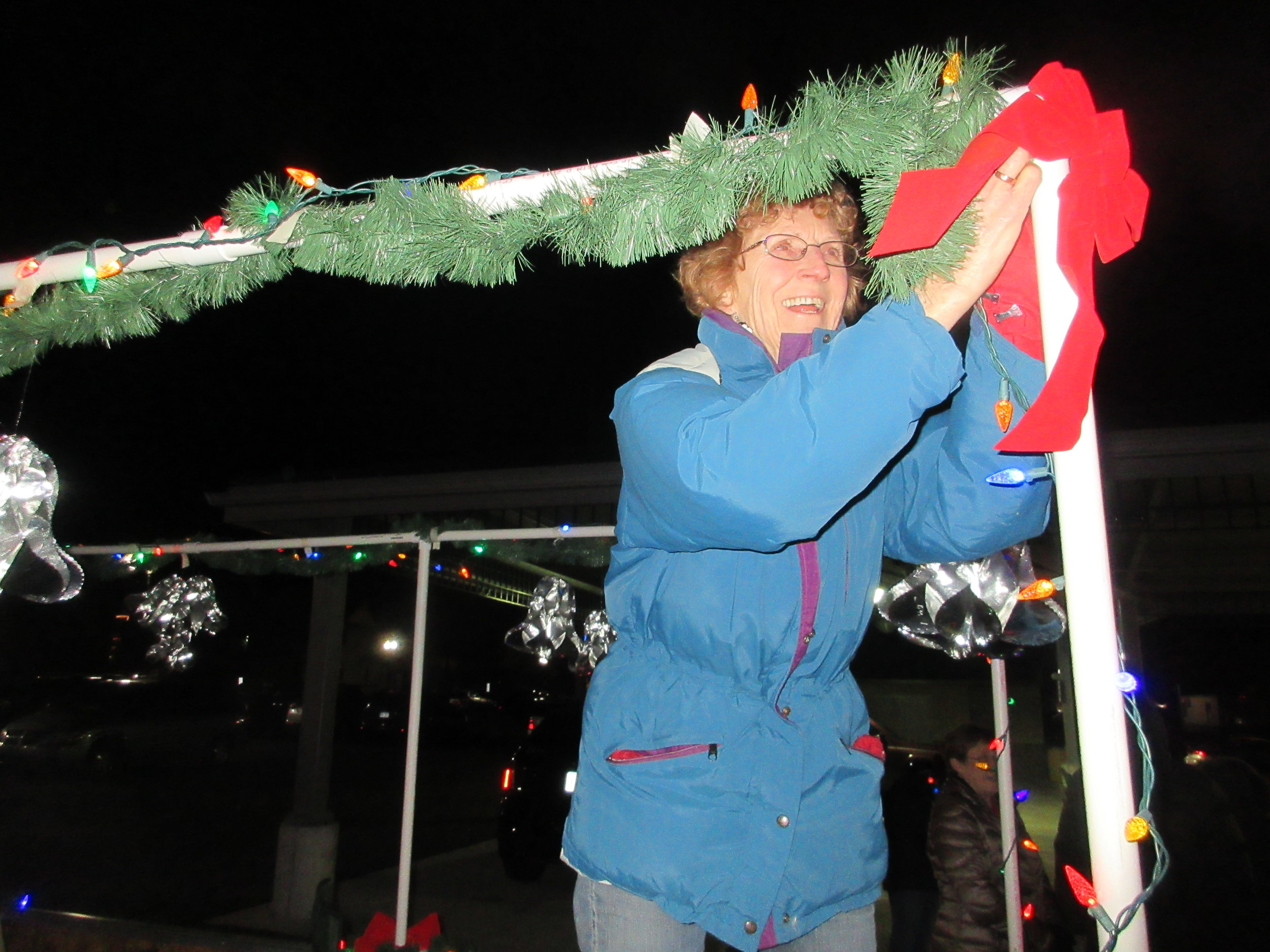 A Civitan decorates a float for a local holiday parade.
