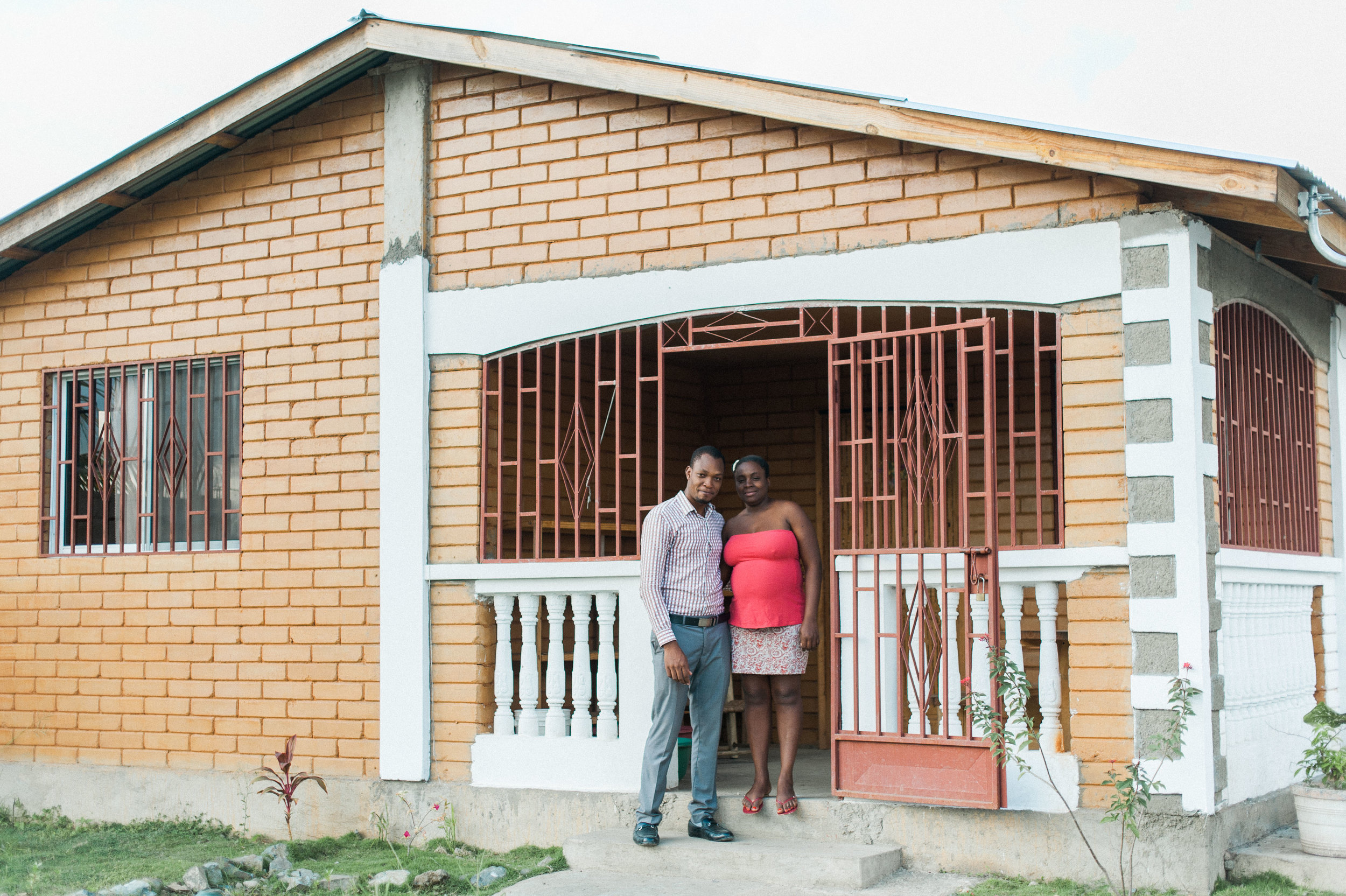 Manuacha and her husband on the front porch of their new earth block home.