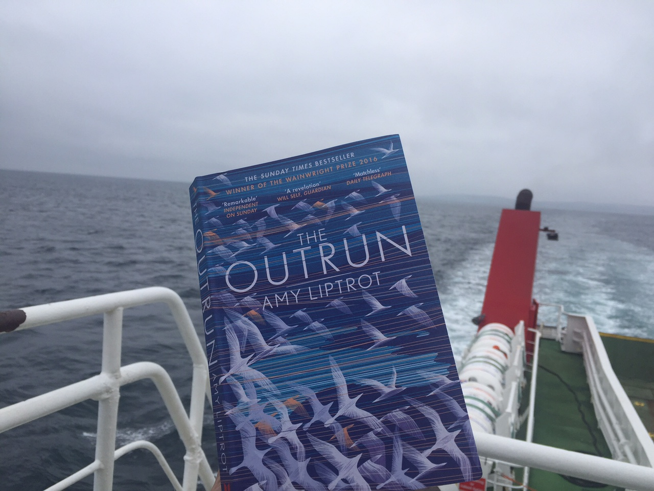 Reading The Outrun on the ro-ro ferry to the Northern isle of Westray