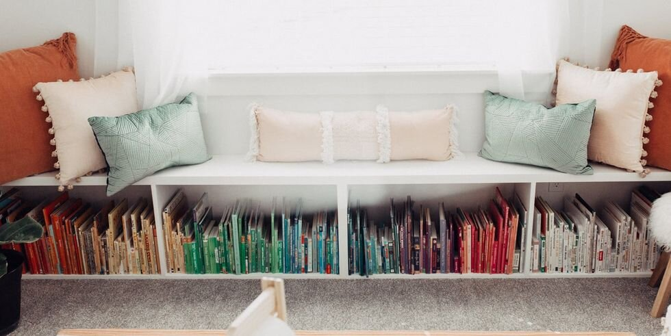 Having a built-in shelf below seating is a functional way to store not only books, but any toys. Throw in a little color coordination and you've got the perfect organization! Via:  Elle Decor