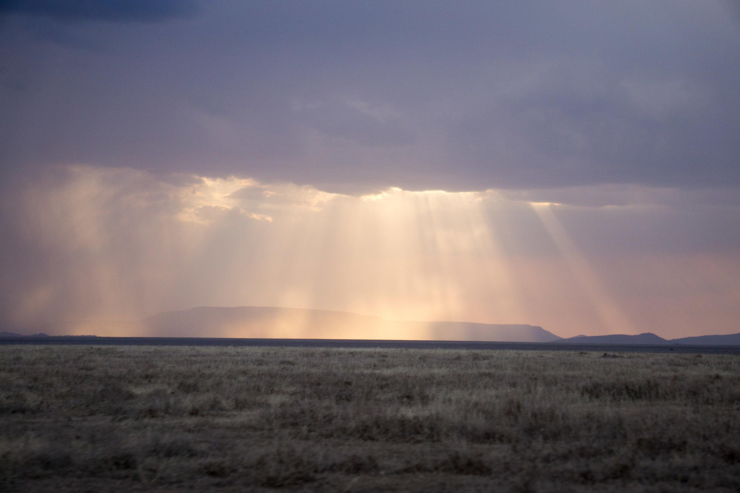 Rain and sun rays across the savannah.