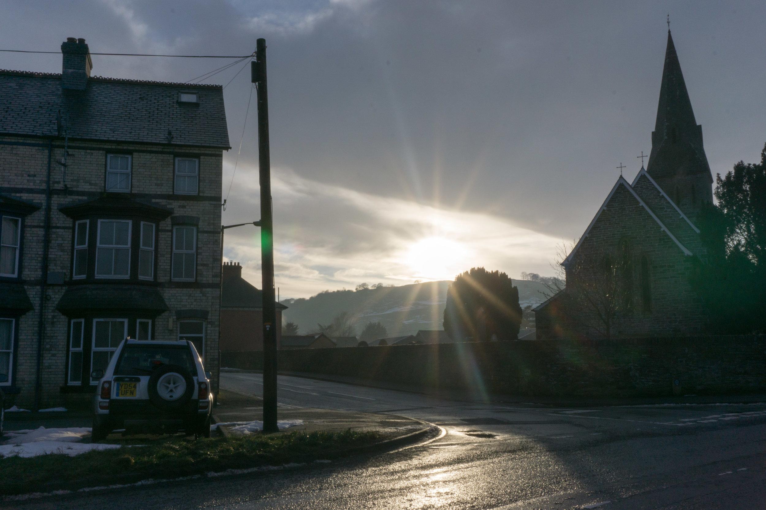 Sun glimmering through a small village