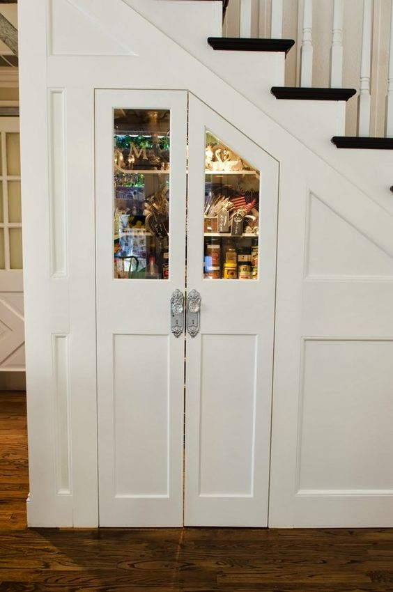 This small angled door has been very craftily built to access the pantry and the glass door adds both beauty, interest as well as functionality