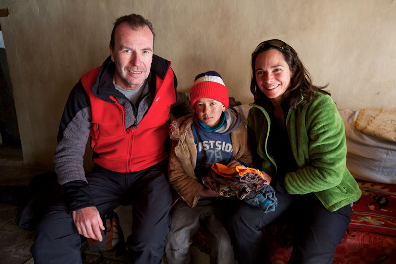 Rolf and Pascale gifting clothes to a young boy in Rumbak.