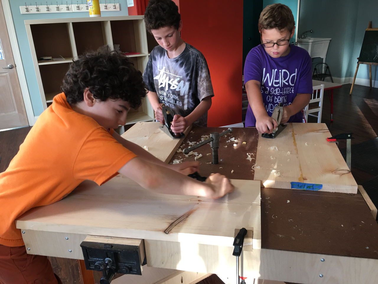 Middle schoolers using hand planes to flatten bench tops in the make a shaker bench program