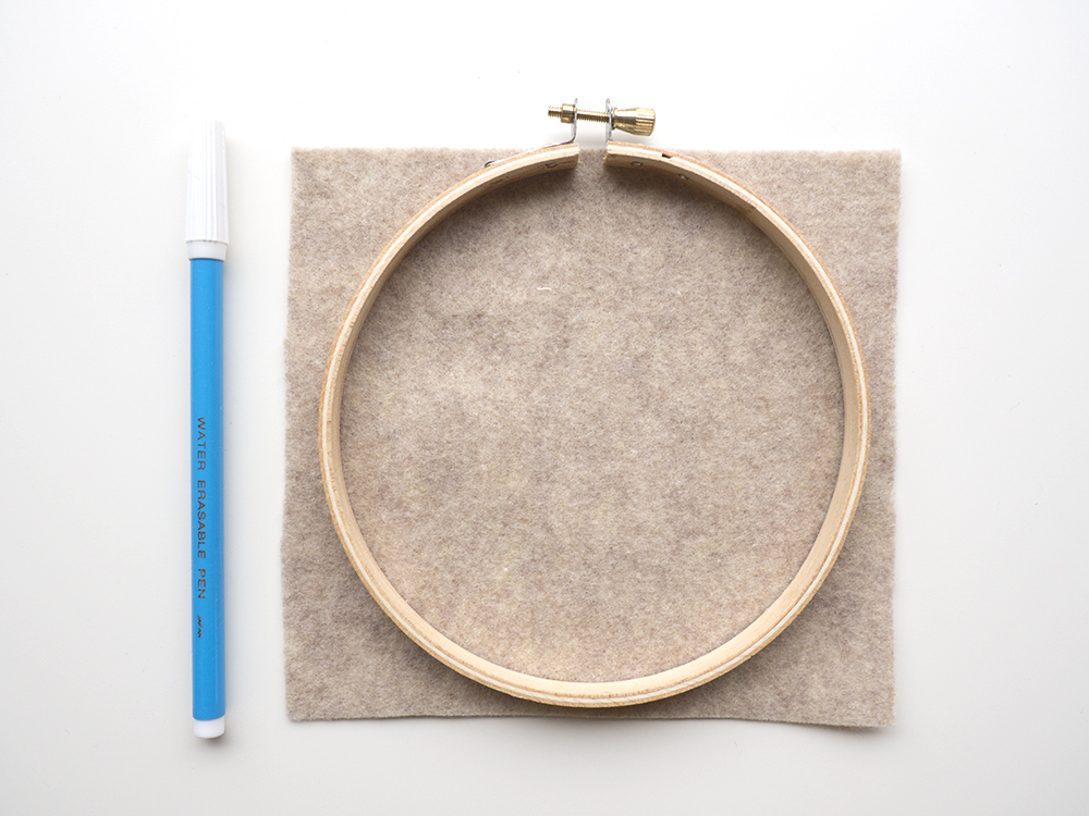 Before you begin backing, trace the embroidery hoop onto the felt. I use an embroidery marker because it easily draws onto fabric, but any type of marker or fabric pen will work. You can trace the inside of the outer hoop, or the outside of the inner hoop. (Both are the same size.) Then set aside.