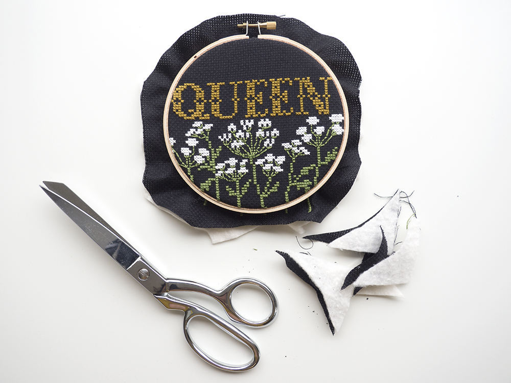"""Trim off the excess fabric (Aida and batting). I casually cut off the corners and not much more. Ideally, the fabric will still extend 1/2"""" - 1"""" outside the hoop edge."""