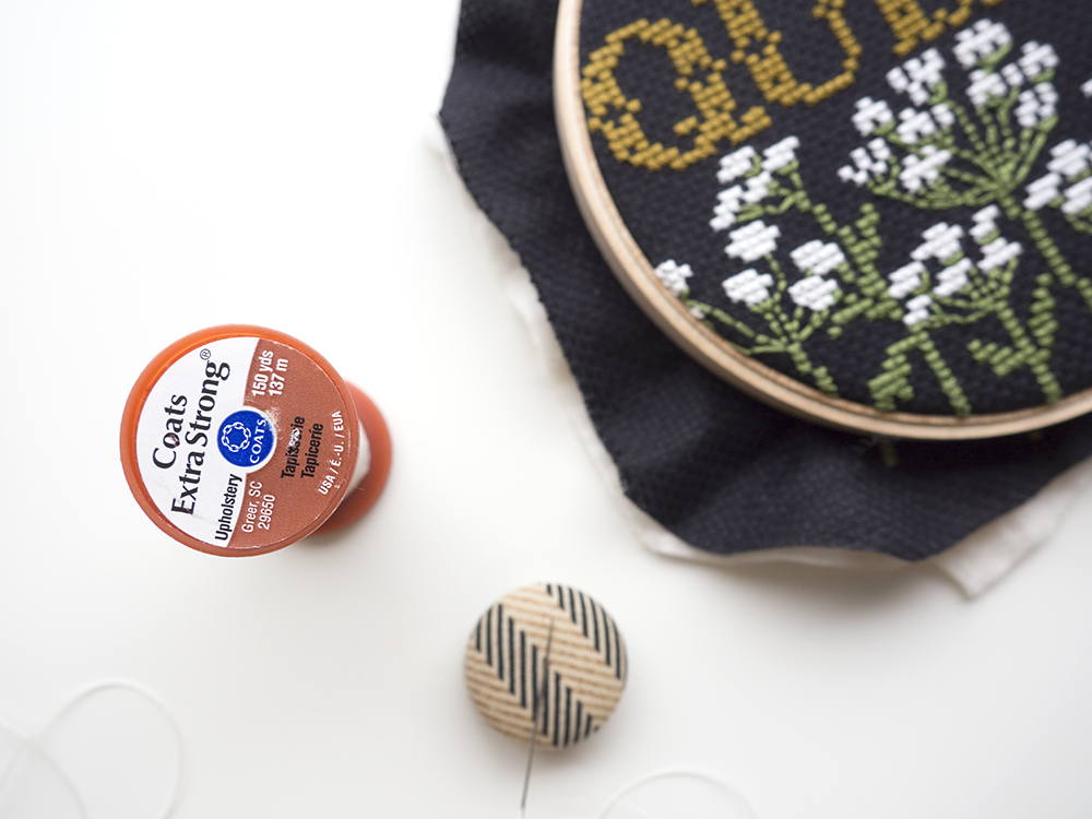 """Thread your needle with waste thread. I prefer Coats Upholstery Thread, but you can use any sort of polyester thread, extra embroidery floss and even DENTAL floss! Tie a knot at the end of the floss leaving a tail you can hold onto (anything longer than 1"""" will be fine)."""