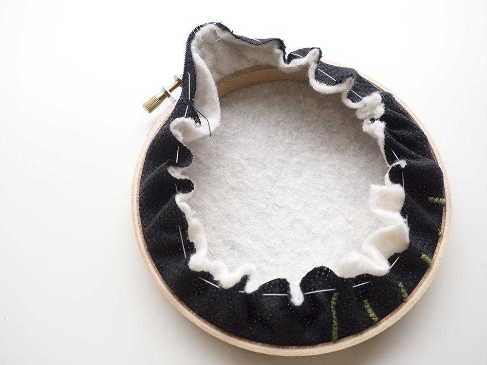 As you pull, the fabric will begin to curl towards the center of the hoop.