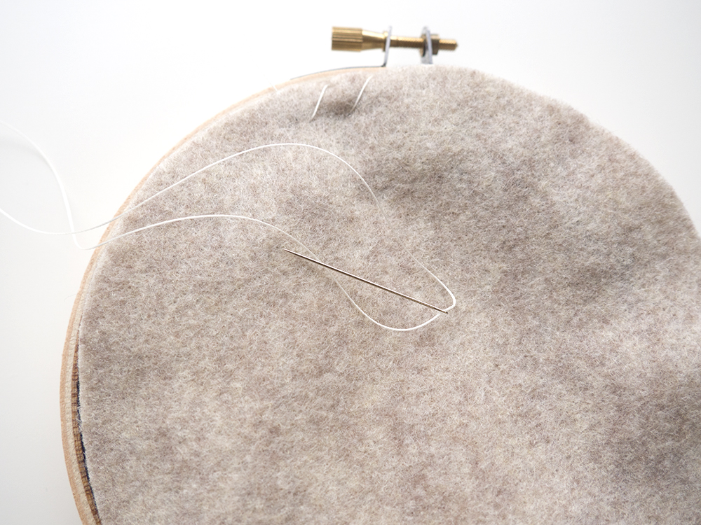 Stitch the felt to the Aida cloth around the edge of the felt. You can use an overcast stitch, whip stitch, blanket stitch, or whatever other stitch might suit your fancy.