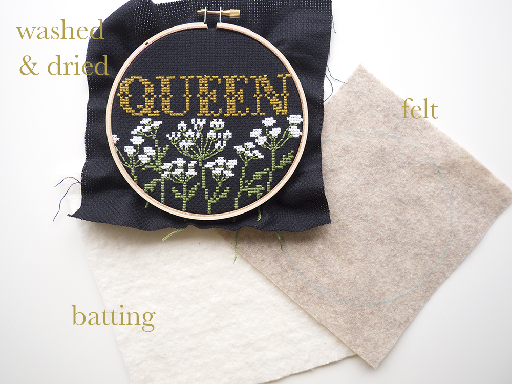 """Each kit comes with organic batting and a piece of felt. The batting is cut to approximately the same size as your Aida cloth and the felt is cut to 1"""" larger than the kit's embroidery hoop. Before you begin backing, make sure your finished stitches are washed and completely dry."""