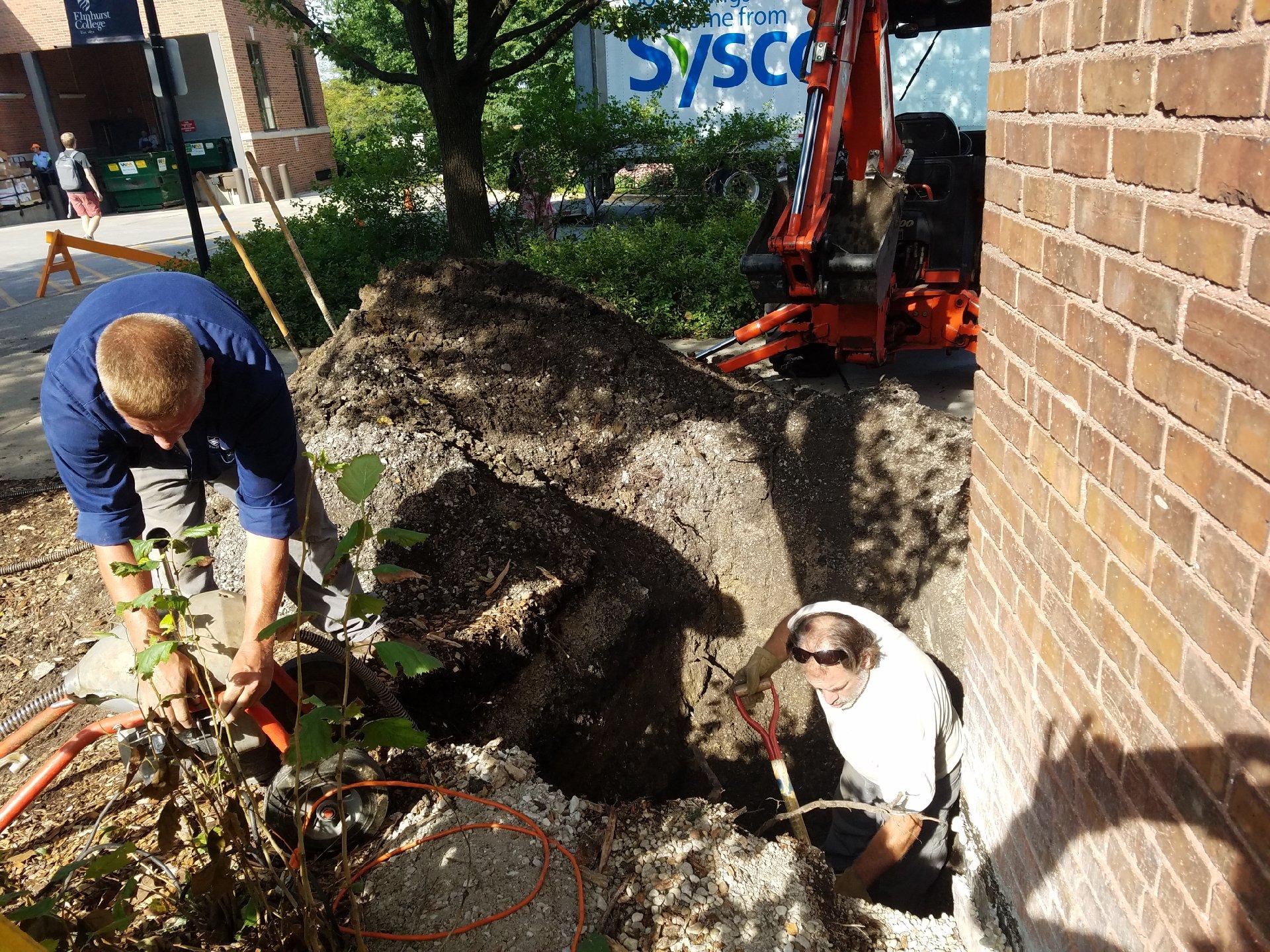 Wade Golz and Robert Mason work on the rain garden outside of Irion Hall. Photo by Gianna Montesano