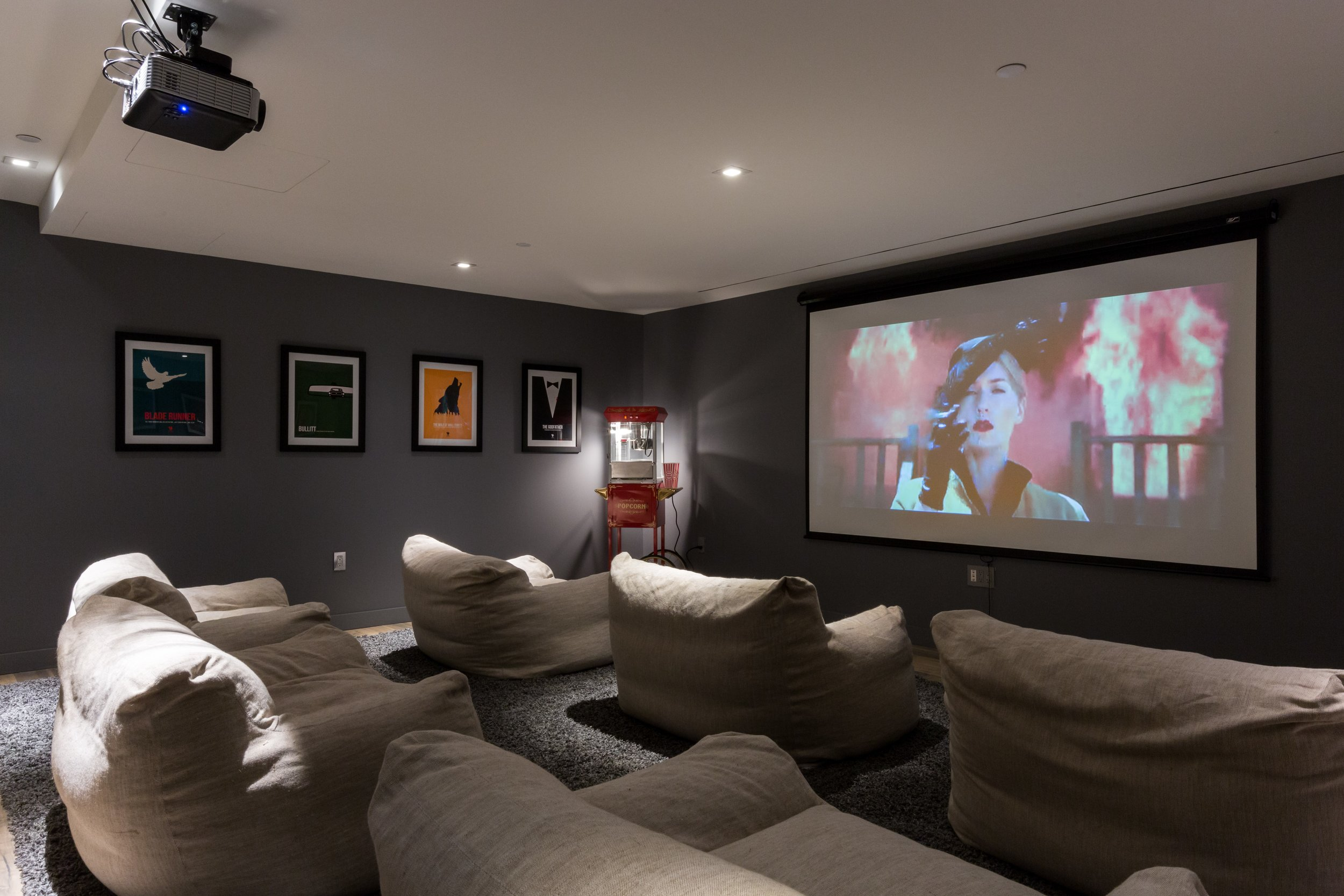 Instead of artwork or photography, we framed vintage movie posters in this basement renovation for an authentic theater impression.