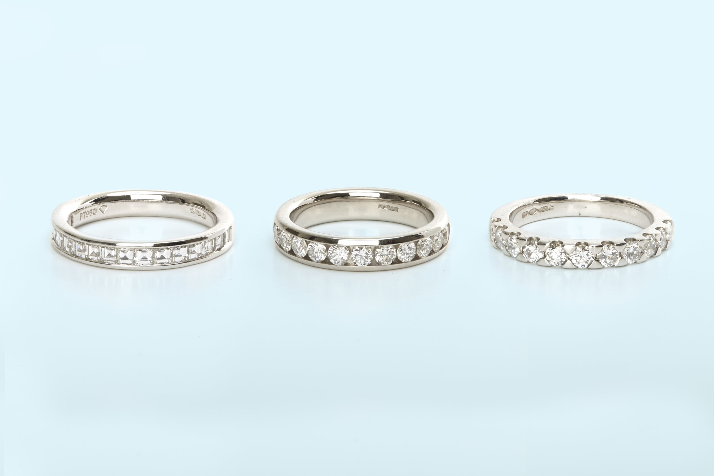 three white gold and diamond rings on pale blue background