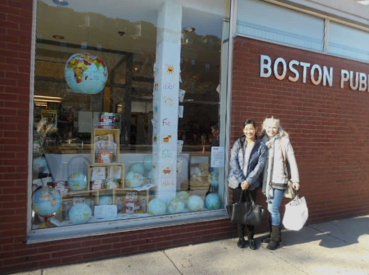 b Local/Focus installers Germaine Choe and Karen Watson in front of the Language Together exhibit