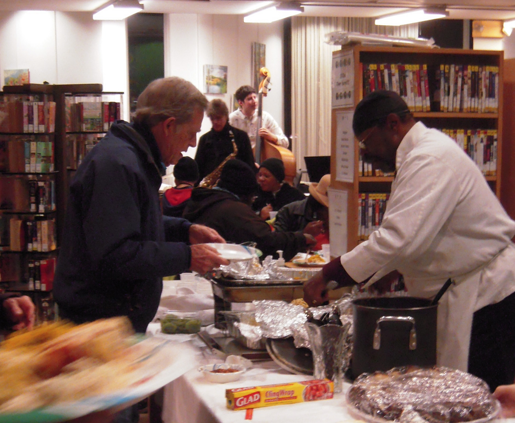 Chef John Hampton serving the holiday dinner at the South End library last year, with Pat Loomis and his Friends in the background.