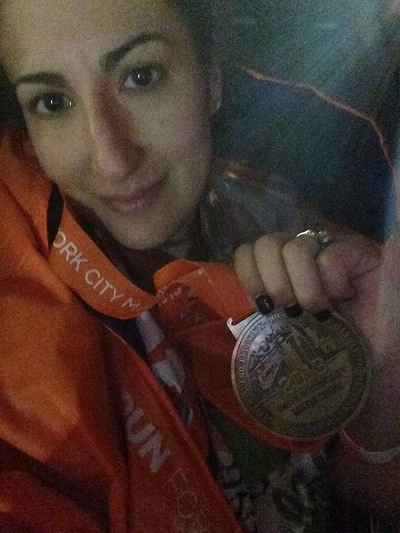 Veronica poses with her medal after finishing