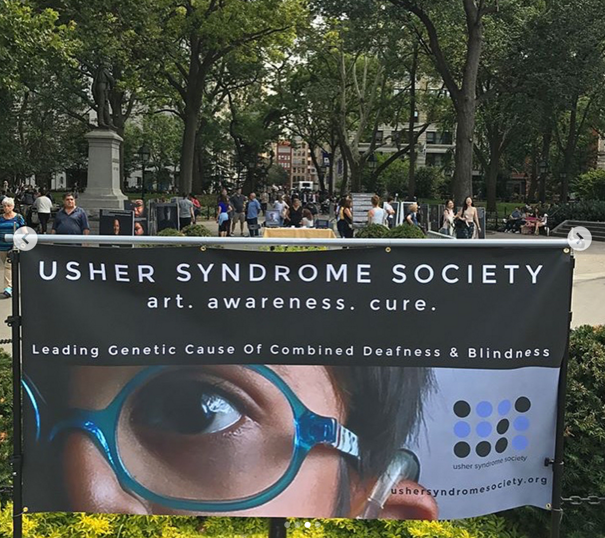 Usher Syndrome Society banner near the portraits in the park. Photo by Rebecca Alexander.