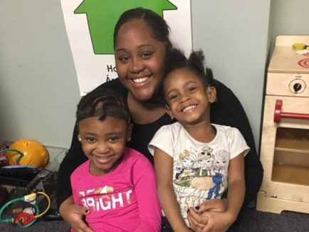 Assistant Teacher Ms. Tiana Brown with two of her preschool students at Clarke.