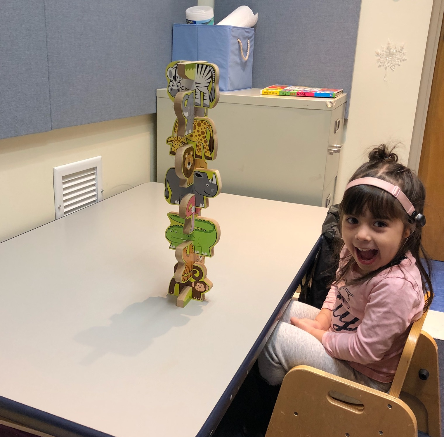 "Fun in speech! One of Sound Start's little learners is excited to see how many jungle animals she can stack, while working on the concepts ""above"" and ""below."" Credit: Kim Reis."