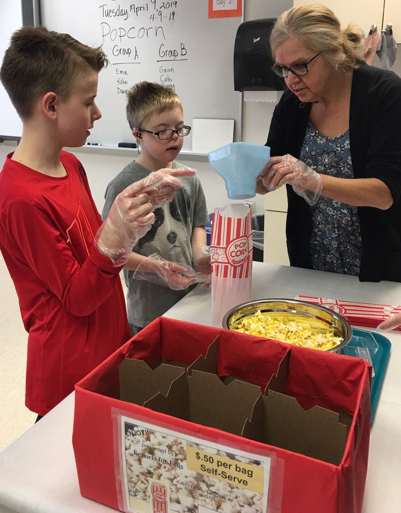 Lisa Olson (teacher) helping students prepare to bag popcorn. 4.8.19 clearance on record. - Copy.jpg