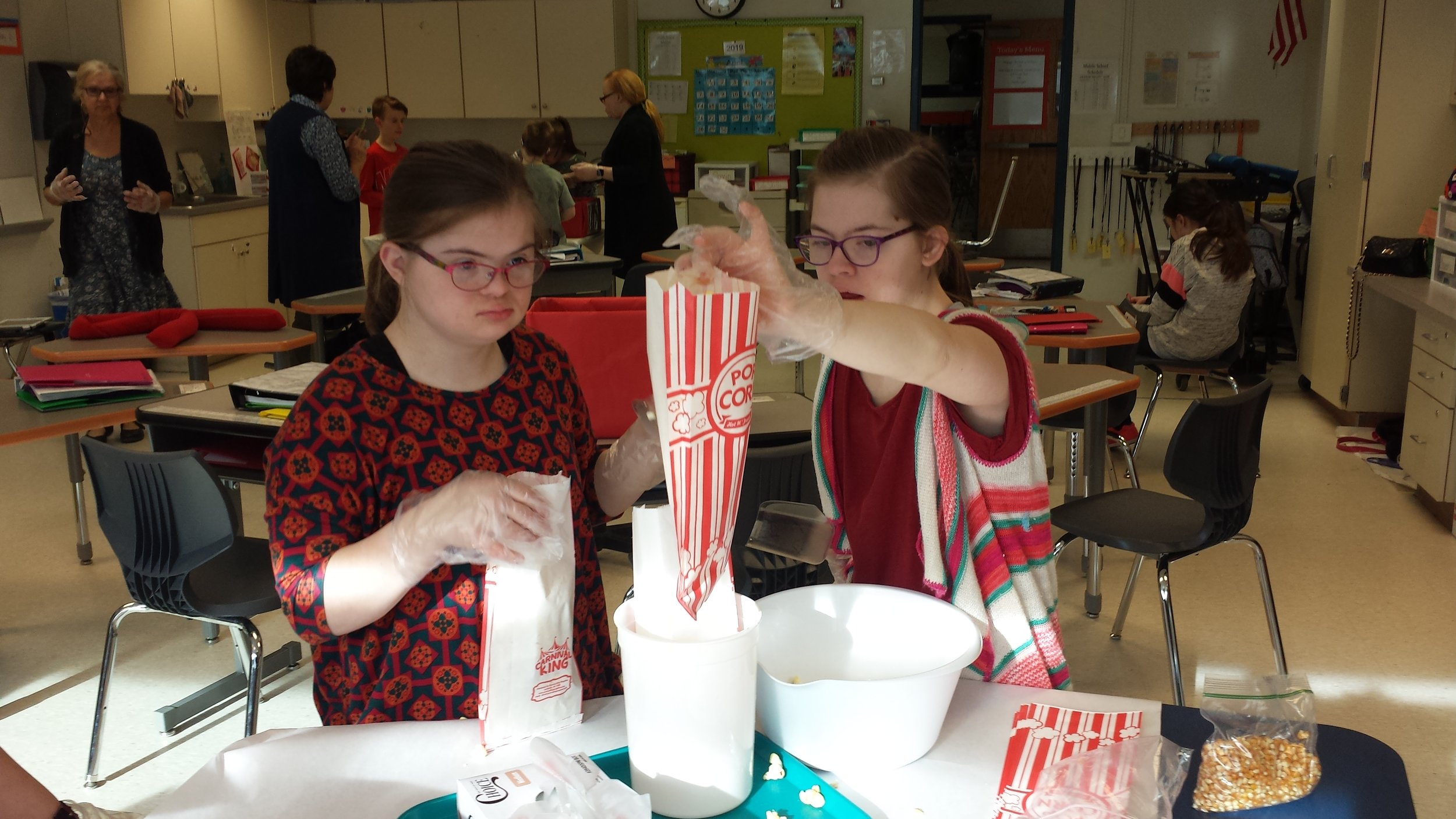 2 girls bagging popcorn approval on record.jpg
