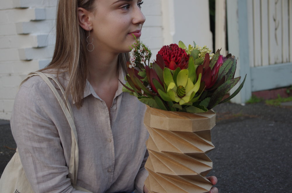 KARTON  A collapsible floral packaging made with unsold flowers and used packaging.