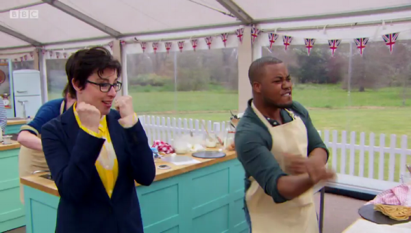 Selasi after flipping a pancake in the pan. Sue is chuffed.