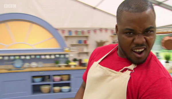 Selasi triumphant after perfecting his lemon curd for his strawberry and lemon roulade.