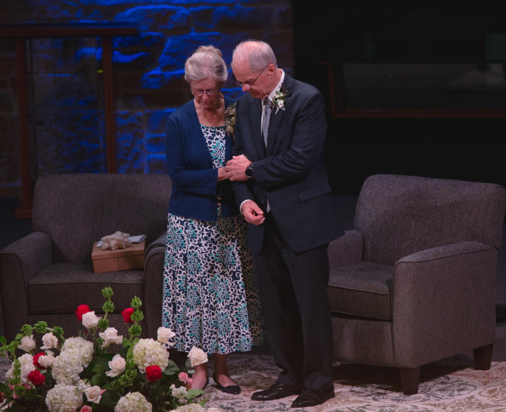Bishop and Diane Tamel praying during their Retirement Celebration.